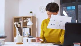 Δημιουργική γυναίκα που εργάζεται στο ενδιάμεσο με τον χρήστη στο γραφείο απόθεμα βίντεο