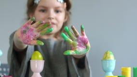 Δημιουργικότητα παιδιών για Πάσχα Κινηματογράφηση σε πρώτο πλάνο των χεριών ενός κοριτσιού που λερώνονται στο πολύχρωμο χρώμα Αυγ φιλμ μικρού μήκους