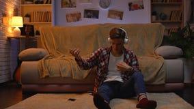 Δημιουργικό αγόρι στα ακουστικά που ακούει τη μουσική που προσποιείται να παίξει την κιθάρα, πάθος απόθεμα βίντεο