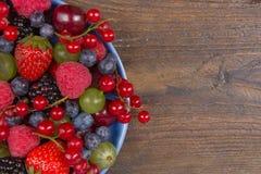 Διάφορα θερινά φρέσκα μούρα σε ένα κύπελλο στον αγροτικό ξύλινο πίνακα Αντιοξειδωτικοοι, detox διατροφή, οργανικά φρούτα Τοπ όψη στοκ εικόνες