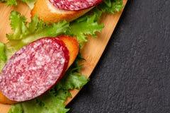 Διάφορα σάντουιτς με το λουκάνικο και το σαλάμι και η σάλτσα στο Μαύρο επιβιβάζονται, υπόβαθρο με το copyspace στοκ φωτογραφία με δικαίωμα ελεύθερης χρήσης