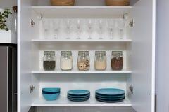 Διάφοροι σπόροι στα βάζα αποθήκευσης στο οψοφυλάκιο, άσπρη σύγχρονη κουζίνα στο υπόβαθρο Έξυπνη οργάνωση κουζινών στοκ εικόνες