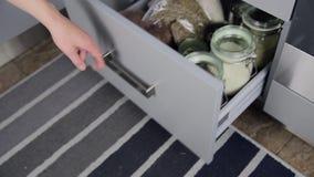 Διάφοροι σπόροι στα βάζα αποθήκευσης στο hutch, άσπρη σύγχρονη κουζίνα στο υπόβαθρο Έξυπνη οργάνωση κουζινών απόθεμα βίντεο