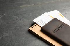 Διαβατήριο, εισιτήρια και σημειωματάριο στο γκρίζο υπόβαθρο, διάστημα για το κείμενο στοκ εικόνες