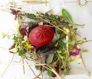 Διακοσμημένο κόκκινο αυγό Πάσχας με τα φρέσκα άγρια λουλούδια και τα χορτάρια στοκ εικόνα με δικαίωμα ελεύθερης χρήσης