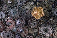 Διακοσμητικά κουμπιά μετάλλων του σκοτεινού μετάλλου και ενός χρυσού κουμπιού ενάντια στο Μαύρο η έννοια ένα λευκό σειρών ενέχυρω στοκ φωτογραφία