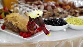 Διακοσμητική πάπια σε έναν εορταστικό πίνακα, που διακοσμείται με τις κόκκινες χάντρες Διακοσμήσεις του εορταστικού πίνακα Πρωτοχ φιλμ μικρού μήκους