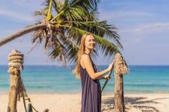 Διακοπές στο τροπικό νησί Γυναίκα στο καπέλο που απολαμβάνει τη θέα θάλασσας από την ξύλινη γέφυρα στοκ φωτογραφία με δικαίωμα ελεύθερης χρήσης
