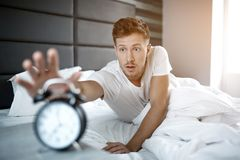Διαταραγμένος νεαρός άνδρας που βρίσκεται στο κρεβάτι στο πρωί Αυτός overslept Ρολόι προσιτότητας τύπων με το χέρι στοκ εικόνες με δικαίωμα ελεύθερης χρήσης