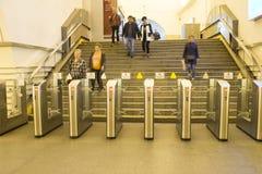 διαφήμιση Οι άνθρωποι πηγαίνουν στη μετάβαση μέσω των ηλεκτρονικών περιστροφικών πυλών στο σταθμό μετρό στη Αγία Πετρούπολη, Ρωσί στοκ φωτογραφία
