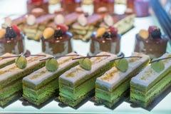 Διαφορετικοί τύποι κέικ στην επίδειξη γυαλιού καταστημάτων ζύμης στο κατάστημα αρτοποιείων στοκ εικόνα
