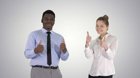 Διεθνείς ευτυχείς χαμογελώντας άνδρας και γυναίκα που παρουσιάζουν αντίχειρες στο υπόβαθρο κλίσης στοκ εικόνα με δικαίωμα ελεύθερης χρήσης