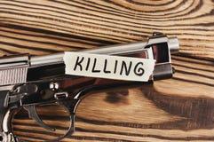 ΔΟΛΟΦΟΝΙΑ επιγραφής σε σχισμένο χαρτί και το στιλπνό πιστόλι στοκ εικόνα