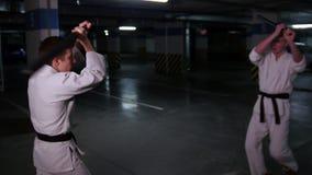 Δύο άτομα στο κιμονό που εκπαιδεύουν τις δεξιότητες kendo τους σε έναν χώρο στάθμευσης Πάλη ξιφών απόθεμα βίντεο