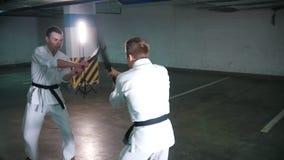 Δύο άτομα στο κιμονό που εκπαιδεύουν το kendo τους σε έναν χώρο στάθμευσης φιλμ μικρού μήκους