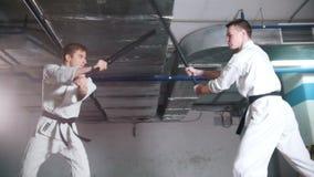 Δύο άτομα στο kendo κατάρτισης κιμονό σε έναν χώρο στάθμευσης Πάλη ξιφών φιλμ μικρού μήκους