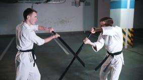 Δύο άτομα που εκπαιδεύουν το kendo σε έναν χώρο στάθμευσης Πάλη ξιφών απόθεμα βίντεο