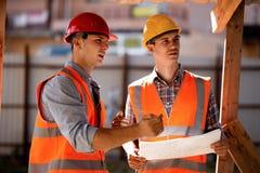 Δύο άτομα που ντύνονται στα πουκάμισα, τις πορτοκαλιά φανέλλες εργασίας και τα κράνη εξερευνούν την τεκμηρίωση κατασκευής στο εργ στοκ εικόνα