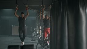 Δύο αθλητικοί νέοι που το τράβηγμα-UPS μαζί στην ευρύχωρη γυμναστική 4k σε αργή κίνηση φιλμ μικρού μήκους