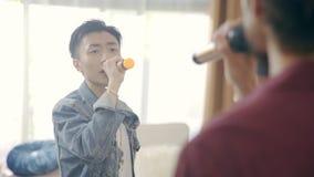 Δύο ασιατικοί τραγουδιστές που προετοιμάζουν το τραγούδι τραγουδιού φιλμ μικρού μήκους