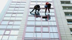 Δύο βιομηχανικοί ορειβάτες είναι πλύσιμο, καθαρίζοντας την πρόσοψη ενός σύγχρονου κτιρίου γραφείων απόθεμα βίντεο