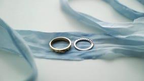 Δύο γαμήλια δαχτυλίδια στην μπλε κορδέλλα απόθεμα βίντεο