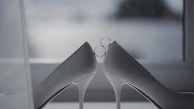 Δύο γαμήλια δαχτυλίδια που κυλούν μαζί κοντά στα γαμήλια παπούτσια της νύφης απόθεμα βίντεο