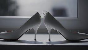 Δύο γαμήλια δαχτυλίδια που κυλούν μαζί κοντά στα γαμήλια παπούτσια της νύφης φιλμ μικρού μήκους