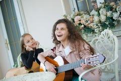Δύο γοητευτικά μικρά κορίτσια με τις κιθάρες στοκ φωτογραφία με δικαίωμα ελεύθερης χρήσης