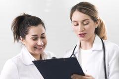 Δύο γυναίκες βοηθοί έντυσαν στα άσπρα παλτά που μιλούν ο ένας στον άλλο στο κέντρο οδοντιατρικής στοκ εικόνες