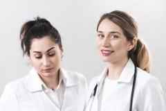 Δύο γυναίκες βοηθοί έντυσαν στα άσπρα παλτά που μιλούν ο ένας στον άλλο στο κέντρο οδοντιατρικής στοκ φωτογραφίες με δικαίωμα ελεύθερης χρήσης
