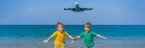 Δύο ευτυχή αγόρια έχουν τη διασκέδαση στην παραλία προσέχοντας τα προσγειωμένος αεροπλάνα Ταξίδι σε ένα αεροπλάνο με την έννοια π στοκ εικόνες