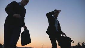 Δύο ευτυχείς νέοι συνάδελφοι με τον αστείο χορό χαρτοφυλάκων περπατώντας μετά από την επιτυχή επιχειρησιακή διαπραγμάτευση στην ο απόθεμα βίντεο
