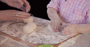 Δύο ζευγάρι των χεριών που κυλούν τις σφαίρες από τη ζύμη και το ψήσιμο απόθεμα βίντεο