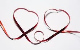 Δύο καρδιές της κόκκινης κορδέλλας στο άσπρο υπόβαθρο στοκ φωτογραφία με δικαίωμα ελεύθερης χρήσης