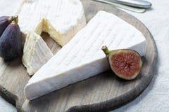 Δύο κομμάτια των γαλλικών μαλακών τυριών Brie και Camembert με την άσπρη φόρμα και την ισχυρή μυρωδιά, που εξυπηρετούνται με τα φ στοκ φωτογραφία με δικαίωμα ελεύθερης χρήσης