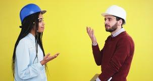 Δύο μηχανικοί πολυ εθνικός τύπος και νέα κυρία τους κάνουν μια συζήτηση για την κατασκευή που φορούν μπλε και άσπρος απόθεμα βίντεο