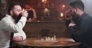 Δύο μοντέρνα άτομα που έχουν μια συνομιλία πέρα από ένα ποτήρι του ουίσκυ και ενός παιχνιδιού σκακιού απόθεμα βίντεο