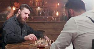 Δύο μοντέρνα άτομα hipster που παίζουν ένα παιχνίδι σκακιού σε έναν φραγμό απόθεμα βίντεο