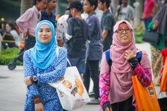 Δύο νέα κορίτσια στα φωτεινά hijabs περπατούν και γελούν κοντά στους πύργους Petronas στοκ φωτογραφία με δικαίωμα ελεύθερης χρήσης
