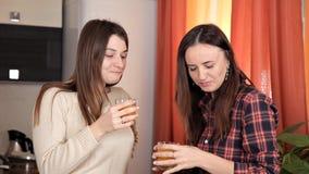 Δύο νέα κορίτσια που κουβεντιάζουν στην κουζίνα και το χυμό από πορτοκάλι κατανάλωσης ενώ το γεύμα προετοιμάζεται φιλμ μικρού μήκους