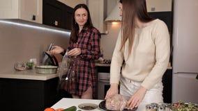 Δύο νέα κορίτσια προετοιμάζουν ένα εορταστικό γεύμα με τα καρυκεύματα κοτόπουλου απόθεμα βίντεο