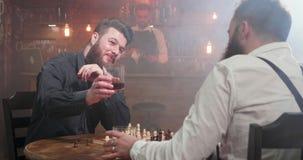 Δύο νέα hipsters που τα ποτήρια του ουίσκυ και του ποτού σε ένα παιχνίδι σκακιού σε ένα μπαρ απόθεμα βίντεο