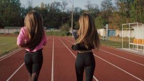 Δύο νέες γυναίκες που οργανώνονται στο στάδιο στο ηλιοβασίλεμα, οπισθοσκόπο απόθεμα βίντεο