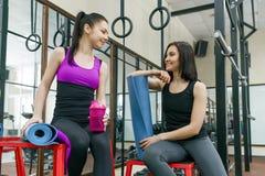 Δύο νέες χαμογελώντας γυναίκες ικανότητας που μιλούν με τα αθλητικά χαλιά στη γυμναστική Κατάρτιση, ομαδική εργασία, υγιής έννοια στοκ εικόνες