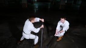 Δύο νεαροί άνδρες στο κιμονό που εκπαιδεύουν τις δεξιότητές τους σε έναν χώρο στάθμευσης Πάλη ξιφών απόθεμα βίντεο