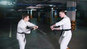 Δύο νεαροί άνδρες στο kendo κατάρτισης κιμονό σε έναν χώρο στάθμευσης απόθεμα βίντεο