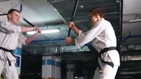 Δύο νεαροί άνδρες στο kendo κατάρτισης κιμονό σε έναν χώρο στάθμευσης Πάλη ξιφών απόθεμα βίντεο
