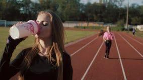 Δύο όμορφες νέες γυναίκες ικανότητας που επιλύουν υπαίθρια Κορίτσια ικανότητας στο στάδιο Στο πρώτο πλάνο, τα ποτά κοριτσιών απόθεμα βίντεο