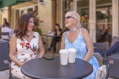 Δύο ώριμες κυρίες απολαμβάνουν ένα φλιτζάνι του καφέ στον υπαίθριο καφέ στοκ εικόνα